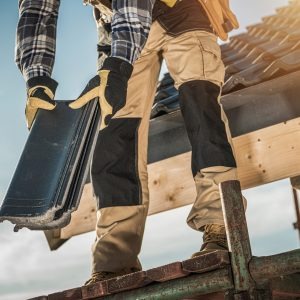 Construction Industry. Roofer with Ceramic Tiles in Hands. Roof Worker Closeup. House Rooftop Covering.